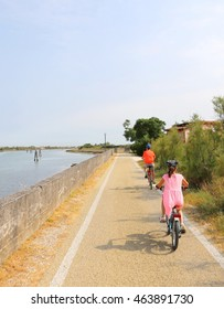 two little boys are riding on the bike path near the lagoon of Venice