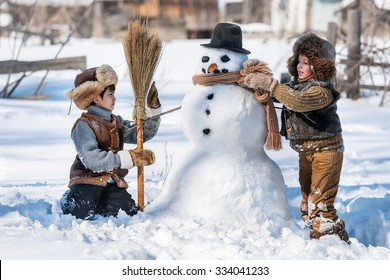 Two little boys sculpt a snowman in the backyard of the house clear winter day