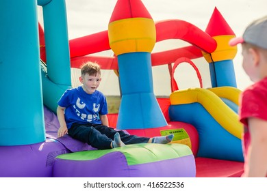 Two little boys in short sleeve shirts playing on inflatable slide and castle outdoors