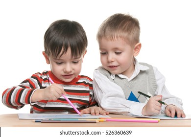 Two little boys are sitting at the desk and write