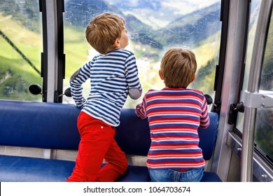 Two little boys sitting inside of cabin of cable car and looking on mountains landscape.