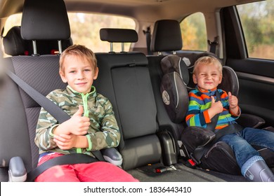 Two little boys sitting on a car seat and a booster seat buckled up in the car. Children's Car Seat Safety