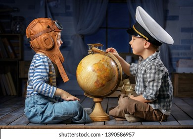 Two little boys in suits of the captain of the ship and the pilot play in the evening in the room