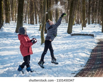 Two little boys throw snow up and have fun in winter park