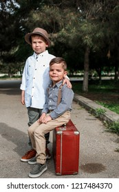 Two little boys in vintage clothes. One is sitting on a vintage suitcase, the other is hugging him