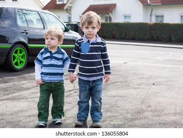 Two little brother toddlers walking on the street