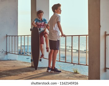 Two little brothers standing with a skateboard near guardrail against the background of the seacoast at a sunset.