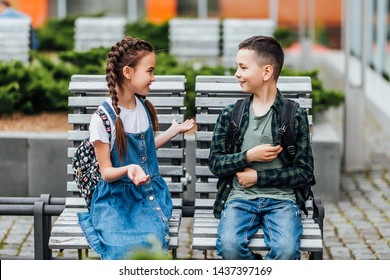 Two , little c hild with backpack sitting on the bench near the school, after finished lesson and speak with each other.