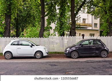 Two little cars parked by a picket fence in Tallinn, Estonia. Black and white in perfect harmony.
