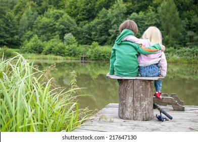 Two little child hug each other and look a the lake view