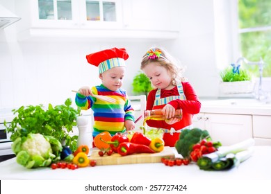 Two little children, adorable toddler girl in red chef hat and apron and funny baby boy preparing healthy lunch making delicious salad with fresh vegetables and garden herbs in a white sunny kitchen