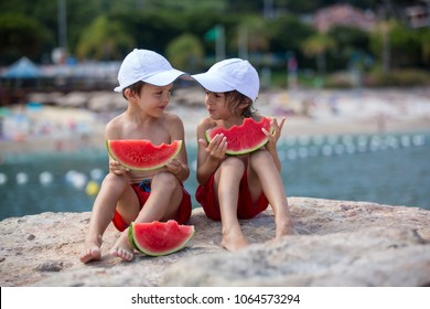 Two little children, boy brothers, eating watermelon on the beach, summertime