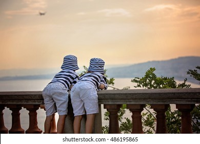 Two little children, boy brothers, looking at landing airplane in the sky over the sea on sunset and dreaming of becoming a pilots