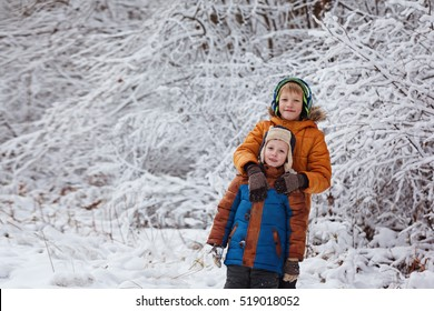 Two little children, boy brothers playing outdoors during snowfall. Active leisure with children in winter on cold days