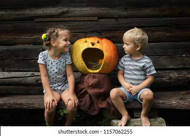 Two little children, boy and girl, sister and brother, sitting near the crying Halloween pumpkin over old wooden wall, funny creative image, outdoor portrait