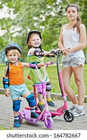 Two little children on scooters and teenage girl in park