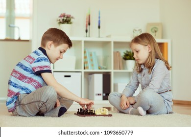 Two little children playing chess at home  emotionally