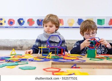 Two little children playing with lots of colorful plastic blocks kit indoors. kid boys having fun with building g geometric figures and learning mathematics in preschool or primary class of school
