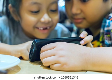 Two little children playing a mobile phone while sitting together at home