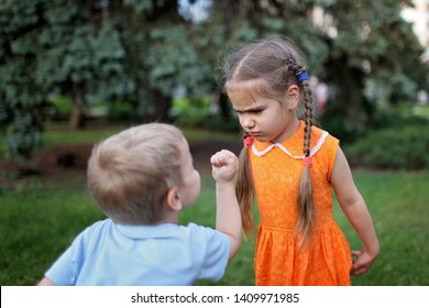 Two little children, sister and brother, quarreling and ready to beat each other crying during their walking, bad mood, negative emotion, upbringing and family concept, summer outdoor