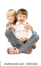 two  little children sitting embrace and smile, on white background, isolated