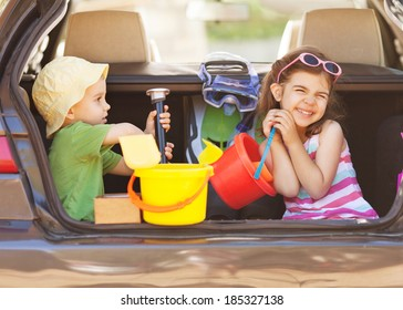 Two little children sitting in th back seat, traveling on summer vacation.
