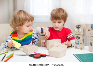two little children together in creativity of the house. Happy kid makes the robot from cardboard boxes. Children's creativity.