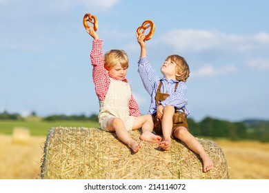 Two little children in traditional German bavarian clothes sitting on hay stack or bale and eating pretzel