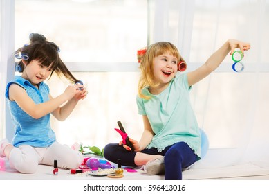 Two little cute girls sit on window sills and playing in hairdressers. Before their makeup accessories. In hair curlers.