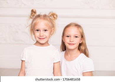 Two little cute sisters pose for a photo standin next to each other. Soft focus