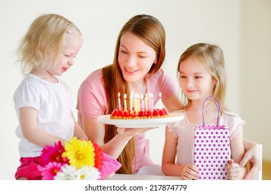 Two little daughters kissing their mother wishing her a happy birthday