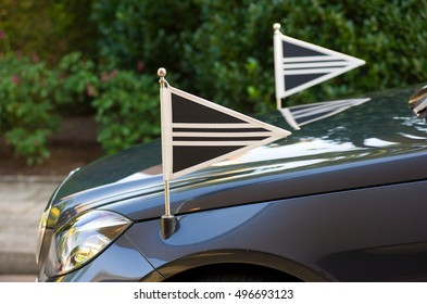 Two little flags on the front of a mourning car
