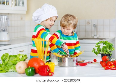 Two little friends cooking italian meal with spaghetti and fresh vegetables in home's kitchen. Sibling children in colorful shirts.