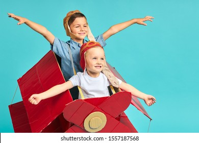 Two little friends flying on toy red airplane, blue sky. Portrait