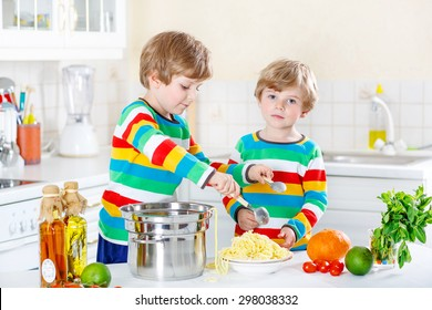 Two little friends preparing healthy meal with spaghetti and fresh vegetables in domestic kitchen, indoors. Sibling children in colorful shirts.