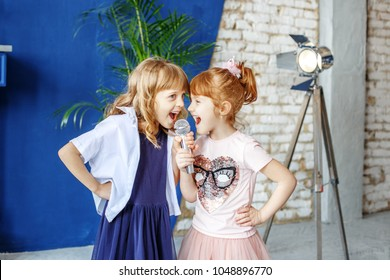 Two little funny children sing a song in a microphone. Group. The concept is childhood, lifestyle, music, singing, friendship.