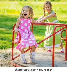 two little funny girls swinging on playgroud speaking with each other