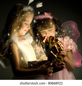 two little girl examine gift in fancy box, smile, on dark background