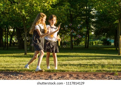Two little girl friends schoolgirl 7-8 years old play with soap bubbles on the meadow in the park