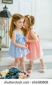 Two little girl friends are whispering, telling secrets. They stand on the white steps at the entrance of the house.