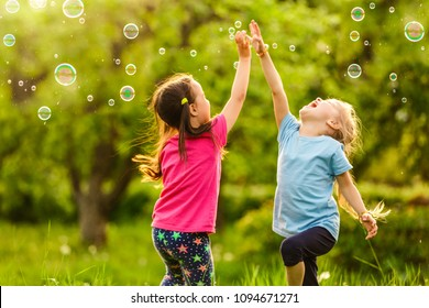Two Little girl fun with soap bubbles in summer park, green fields, nature background, spring season