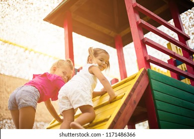 Two little girl  playing together on playground. Space for copy.