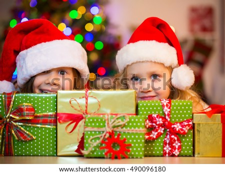 0b63cbd383fd3 Two little girl in Santa hat hiding behind presents under the Christmas tree