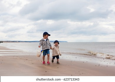 Two little girl walking along the beach in a low tide, Pevensey bay, England, selective focus