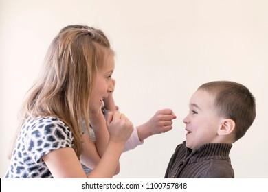 Two little girls beat the boy. Light background. European appearance.