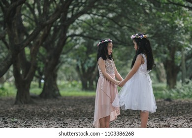 Two little girls in a beautiful dress in a park at sunset in Hanoi, Vietnam.