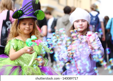 Two little girls blow a lot of soap bubbles in the street on the holiday of spring and bubbles Dreamflash