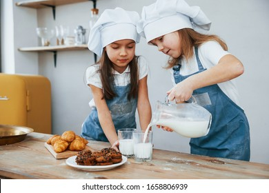 Two little girls in blue chef uniform pouring milk into glasses on the kitchen with cookies on table.