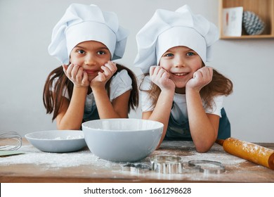 Two little girls in blue chef uniform smiling together on the kitchen.