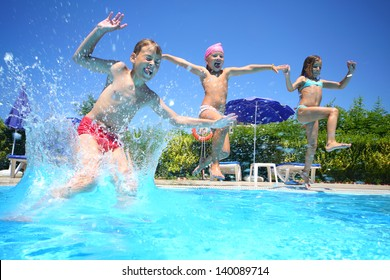Two little girls and boy fun jumping into the swimming pool, shot through the underwater package.